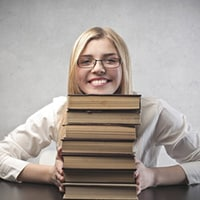Woman with pile of books learning how to publish your book